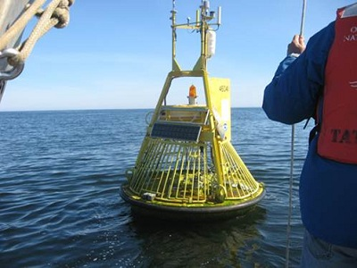 Yellow instrument being hauled out of water onto a ship