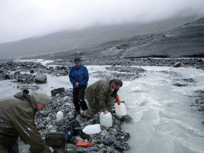 Three people taking water samples from a partly frozen stream