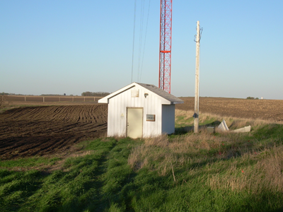 Small shed on a field with a tower behind it