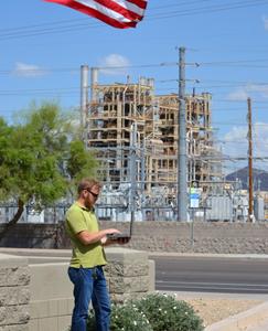 Man standing in front of power plant, holding an instrument